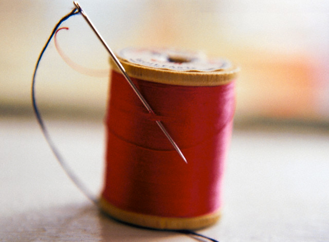 Spool of thread and sewing needle --- Image by © Cheryl North Coughlan/Corbis
